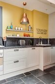Kitchen counter with granite worksurface below two grey shelves mounted on yellow wall