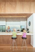 Children sitting on barstools and mother behind free-standing counter in modern kitchen with suspended wooden ceiling