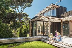 Mother and children on sunny wooden terrace with pergola outside modern wooden house