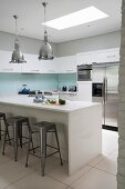 Island counter, dining area and bar stools in white modern kitchen