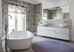 Free-standing bathtub and patterned wallpaper in elegant bathroom