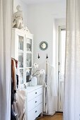 White cupboard with glass doors seen through curtains