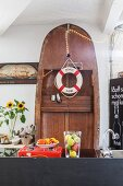 Wooden boat stood on end behind kitchen counter decorated with lifebelt and fairy lights