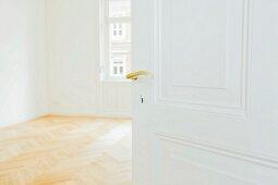 Empty room seen through open door