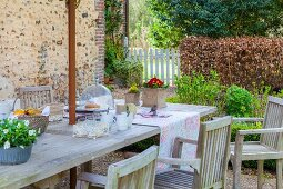 Garden table set with spring flowers and wooden chairs on rustic terrace