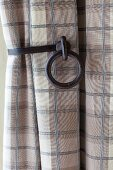 Cast-iron curtain holdback holding checked curtain in shades of beige