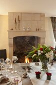 Flower arrangement on festively set dining table and view of open fire
