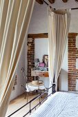 Canopied bed in front of vintage-style dressing table and armchair in renovated farmhouse
