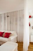 White curtain partition around loose-covered sofa and pouffe