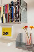 Framed lettering above white floating shelf and books and glass vase on metal shelves