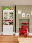 Red rocking chair in niche next to kitchen dresser