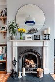 Round mirror above open fireplace with classic surround