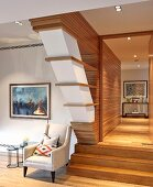 Armchair in hallway below sloping wood-clad wall
