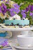 Blaue Heidelbeertorte vor einem Strauß mit Glockenblumen