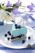 Stück Heidelbeertorte auf blau-weiß gedecktem Tisch