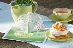 Frühlingshaft gedeckter Tisch mit grünem Service und Einladungskarte