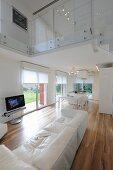 Eleganter, offener Wohnraum mit weisser Ledercouch und Edelholzparkett, Blick auf Glasbrüstung am oberen Etage