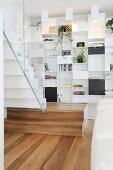 Weisses Designer-Einbauregal und Treppe mit Glasbalustrade