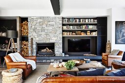 Living room in natural tones with leather sofa and open fireplace