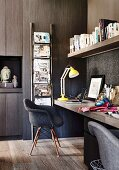 Dark office with clad wall and yellow desk lamp