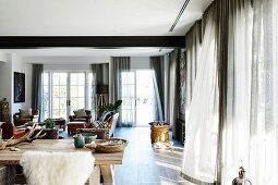 Light shines through lattice windows into the living room in natural tones