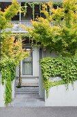 Facade cutout with nostalgic balcony railing and green, gray garden wall