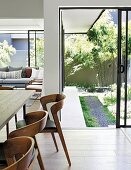 Modern wooden chairs in front of open terrace doors leading to garden