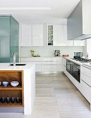 White glossy kitchen cupboards, island counter and stone-tiled floor