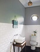Two-tone wall with porthole window above toilet