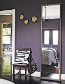 Narrow full-length mirror in bedroom with black walls