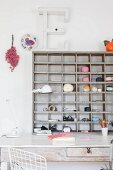 Balls of yarn and office utensils on wooden shelves above vintage desk