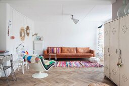 Leather couch, colourful rug and retro easy chair in living area