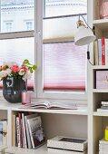 Plissee-Scheibenvorhang als Sichtschutz am Fenster in maßgefertigtem Bücherregal