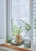 Fensterbrett aus rustikalem Eichenholz mit Vasen und Teelichtgläsern dekoriet, an Fenster romantische Häkelspitze