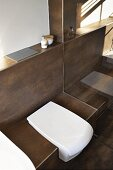 A white toilet integrated into a tiled brown bench with a flush plate embedded in the wall panel