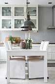 White dining table and chairs with loose covers in kitchen