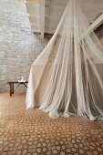 Mosquito net over bed in restored period building with Mediterranean ambiance