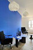 Schwarzer Armlehnstühle und blauer Designertisch vor gleichfarbigem Raumteiler