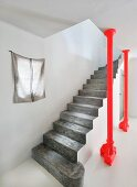 Concrete staircase next to red steel column