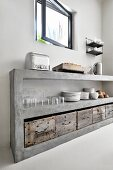Crockery and glasses stacked on concrete kitchen shelves above rustic wooden crates below open window