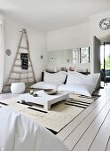 White beanbags, low coffee table and rustic wooden frame in comfortable lounge