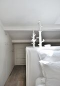 Space-saving fitted cupboards under sloping ceiling and artistic candlesticks in white bedroom