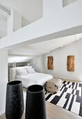 Objets d'art made from bark, black vases and black and white rug in white bedroom