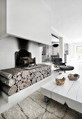 Low white coffee table in front of rustic fireplace with chimney breast