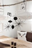 Black and white Christmas decorations hung from branch above dining table