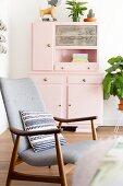 Retrosessel mit gemustertem Kissen vor rosafarbenem Küchenbuffet