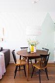 Runder Holztisch mit alten Windsorstühlen