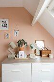 Ornaments on top of chest of drawers against salmon-pink wall
