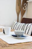 Breakfast place setting of bowl and plate on wooden table