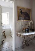 Exquisite antique console table with marble top below painting of bird